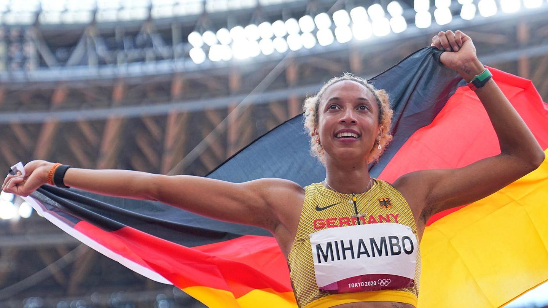 """Eine farbige junge Frau im Leichtathletik-Dress und """"Mihambo"""" als Startnummer jubelt mit deutscher Flagge über dem Kopf"""