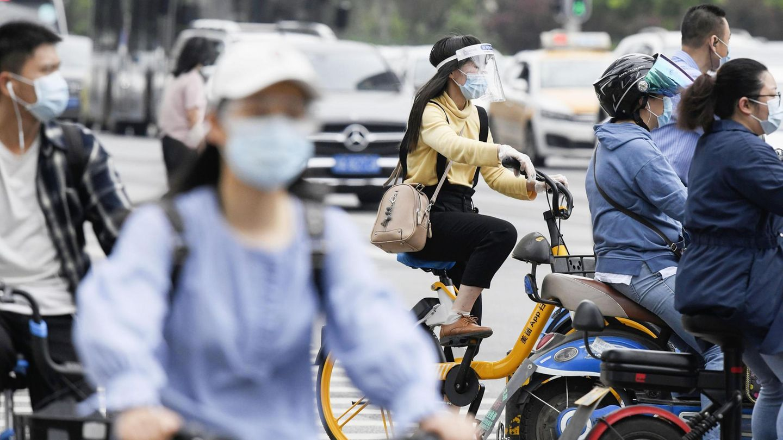 Wuhan, China.Menschen tragen Mund-Nasenbedeckungen auf dem Weg zur Arbeit