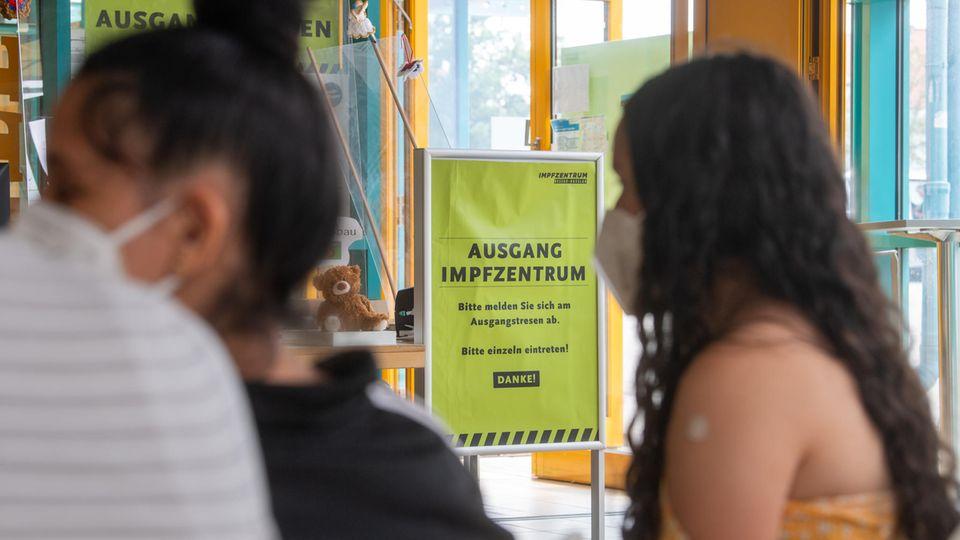 Ein Mädchen mit langen, schwarzen Locken sitzt in gelbem Top und mit einem Pflaster auf dem linken Oberarm im Warteraum