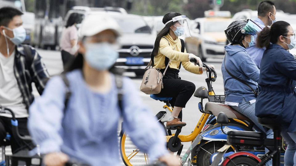China, Wuhan: Menschen tragen Mund-Nasenbedeckungen