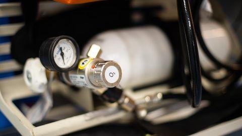 """Eine Gasflasche mit Druckanzeige trägt auf dem Metall-Ventil einen runden, weißen Aufkleber mit """"O2""""-Aufdruck"""