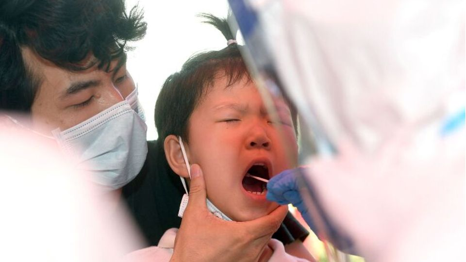 In Wuhan wird ein Kind auf das Coronavirus getestet, ein Erwachsener hält seinen Kopf, ein anderer testet im Rachen