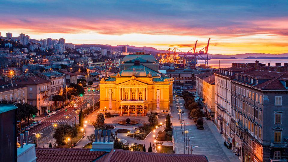Blick über eine Stadt in der Abenddämmerung: ein Prachtbau mit Säulenportal in der Bildmitte, im Hintergrund Hafenkräne