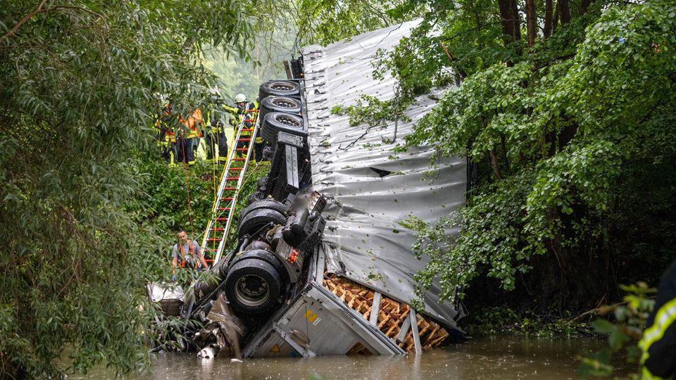 Ein Lkw liegt zwischen Bäumen auf der Seite, das Führerhaus ist zum Großteil in einem Gewässer versunken, Retter stehen daneben