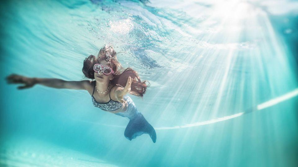 Ein Mädchen trägt eine Meerjungfrauenflosse