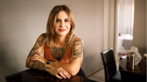 Eine Frau mit vielen Tattoos an Armen und Oberkörper