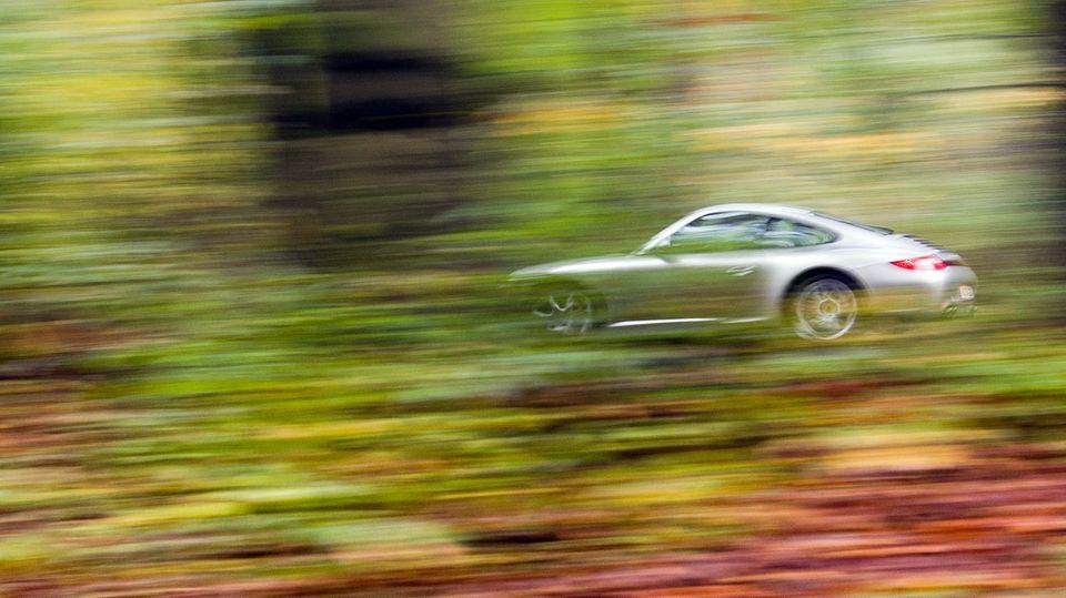 Ein Porsche fährt durch den herbstlich verfärbten Wald