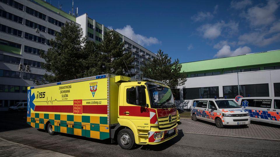 Ein leuchtend gelb und rot lackierter Rettungswagen mit tschechischer Beschriftung steht vor einem mehrstöckigen Krankenhaus