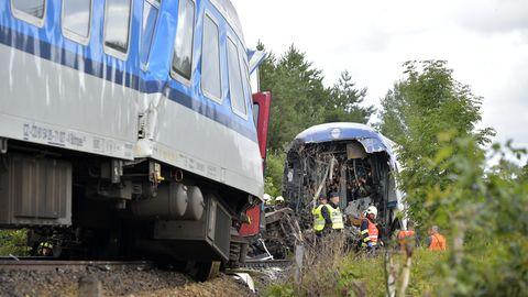 Rettungskräfte in gelben und orangen Warnwesten stehen zwischen einem gestauchten und einem am Ende offenen Zugwaggon