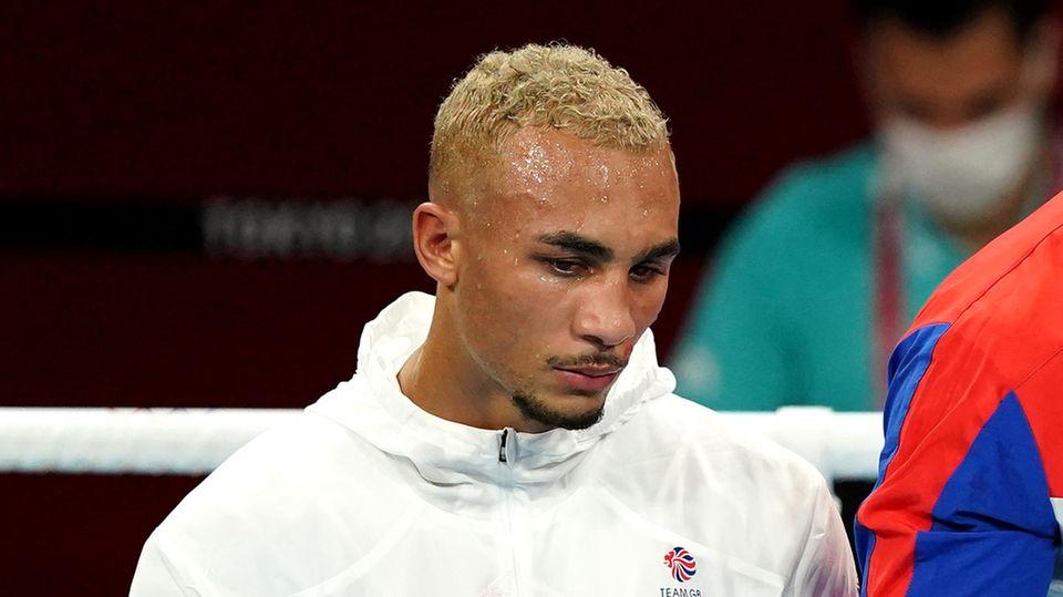 Ein farbiger Mann mit blondierten Locken steht in weißem Trainingsblouson und enttäuschtem Gesichtsausdruck in einem Boxring