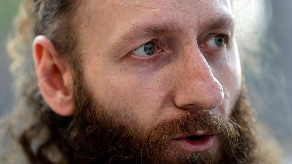 Ein weißer Mann mit langen, rotbraunen Locken und Vollbart spricht und schaut dabei an der Kamera vorbei