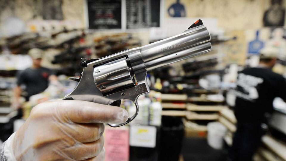 Eine rechte, weiße Männerhand in einem durchsichtigen Gummihandschuh hält einen silbernen Revolver mit kurzem Lauf