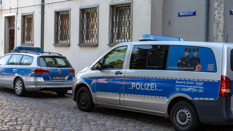 Polizeiwagen stehen auf einer mit Kopfsteinpflaster gepflasterten Straße