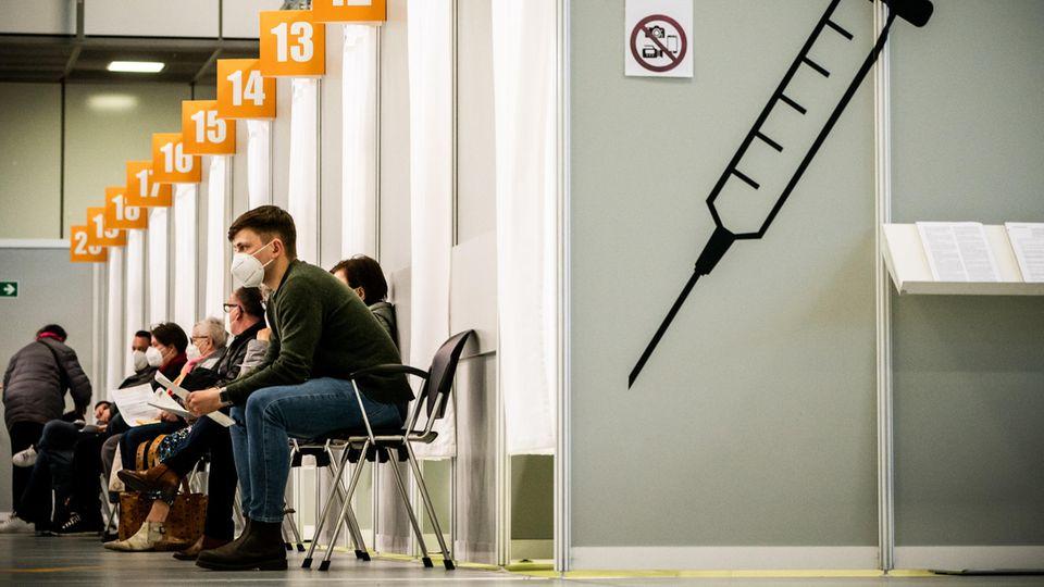 Berlin: Menschen warten im Corona-Impfzentrum auf dem Messegelände auf ihre Impfung