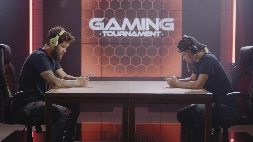 Gaming-Handy: Zwei Kontrahenten sitzen sich gegenüber und spielen am Smartphone.