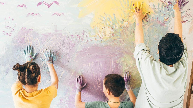 Mutter und zwei Kinder bemalen eine Wand mit den Händen