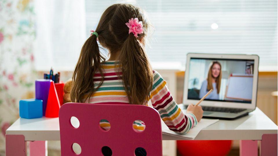 Schülerin am Schreibtisch mit Lehrerin auf dem Laptop