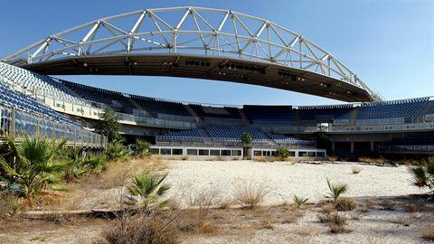 ...glauben, dass die Olympischen Spiele in Athen einer der Faktoren waren, die Griechenland finanziell in die Knie gezwungen haben. Hier zu sehen: die verlassene Beachvolleyball-Arena, aufgenommen zehn Jahre nach den Spielen 2004. Hier holt sich die Natur ihren Lebensraum langsam zurück.