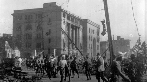 Ein Foto in Schwarzweiß zeigt Menschen, die an einem stark zerstörten Gebäude vorbeigehen