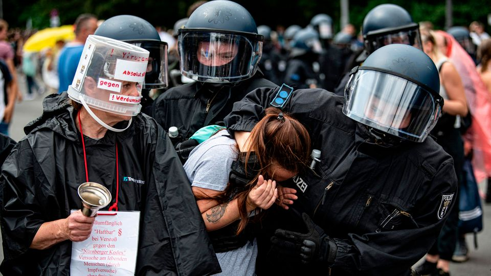 Ein Polizist in voller Kampfmontur nimmt eine Frau mit braunem Pferdeschwanz in den Schwitzkasten