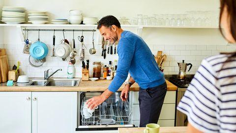 Mann räumt Geschirrspüler ein