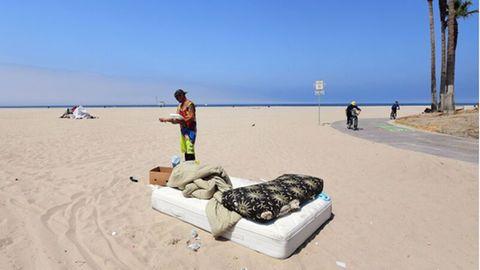 Ein Mann steht am Strand und liest, davor ist eine Matratze mit Decken zu sehen