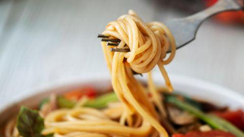 Spaghetti werden auf eine Gabel aufgewickelt.