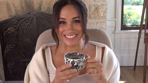 Meghan Markle lächelt und hält eine Tasse Tee in die Kamera