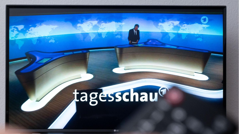Während im Hintergrund auf einem TV-Gerät die Tagesschau beginnt, hält im Vordergrund eine linke Hand eine Fernbedienung