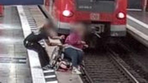 Ein Mann hält eine Rollstuhlfahrerin fest, um den Absturz ins Gleisbett zu verhindern