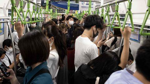 In einem vollen Waggon stehen Japanerinnen und Japaner dicht an dicht und halten sich an grünen, dreieckigen Haltegriffen fest