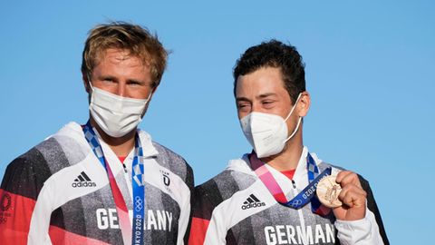 Ein blonder weißer Mann und ein dunkelhaariger weißer Mann stehen mit Bronze-Medaillen um den Hals vor blauem Himmel