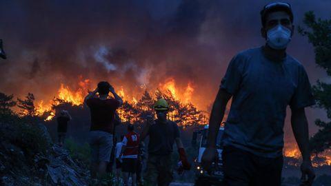 Einsatzkräfte gehen nach einem Einsatz in der Nähe des Dorfes Akcayaka, während im Hintergrund das Feuer eines Waldbrandes wütet