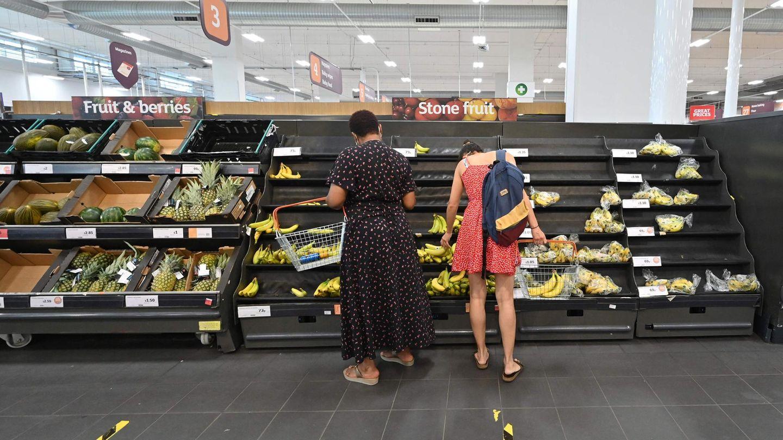 Kunden eines Supermarkts in Großbritannien stehen vor halbleeren Regalen: