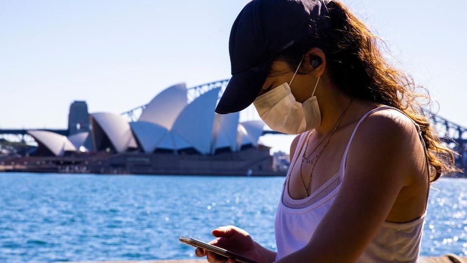 Während des neuen Lockdowns in Sydney spaziert eine Frau mit Mobiltelefon im Royal Botanical Garden