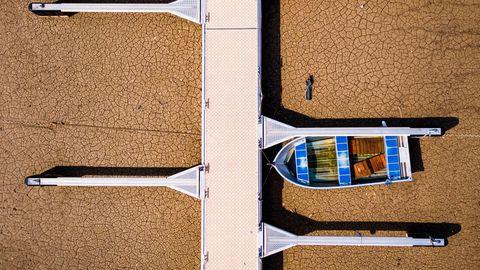 Ein gestrandetes Boot steht an einem Pier am Ufer des Greyerzersee