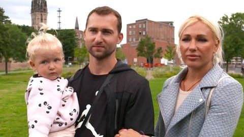 Das weißrussische Paar steht mit ihrer Tochter auf einer Wiese in Deutschland
