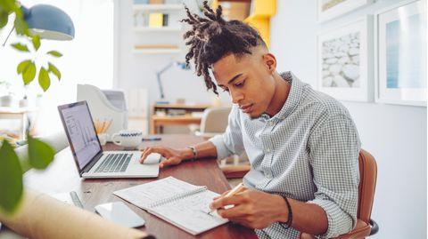 Laptop für Studenten: Ein Student sitzt am Laptop, notiert aber etwas per Hand auf seinem Block.