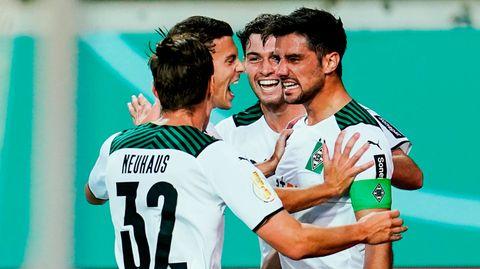 Vier Fußballspieler in weißen Trikots und Hosen jubeln gemeinsam