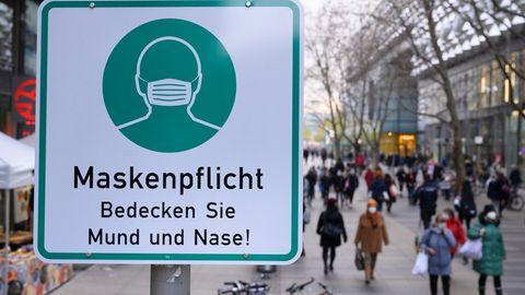 Ein Hinweisschild auf die Maskenpflicht hängt auf der Einkaufsstraße Prager Straße an einem Lampenmas
