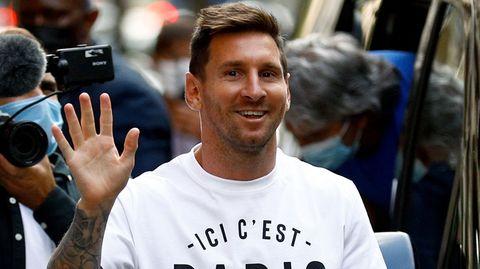 """Ein weißer Mann mit braunem Seitenscheitel trägt ein weißes T-Shirt  mit """"Ici c'est Paris""""-Aufdruck und winkt freundlich"""