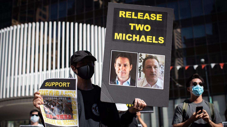 Eine Person hält ein Schild mit Fotos von Michael Kovrig und Michael Spavor