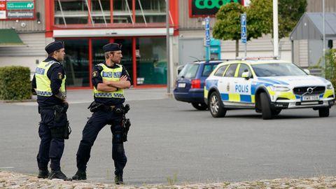 Zwei Polizisten sichern nach Schüssenauf einem Parkplatz imKristianstader Stadtteil Nasby den Tatort