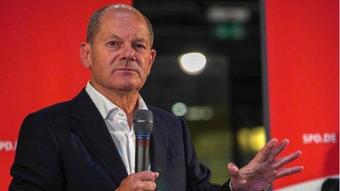 Ein weißer älterer Mann mit Halbglatze steht in Jackett und weißem Hemd auf einer Bühne. Mit Rechts hält er ein schwarzes Mikro