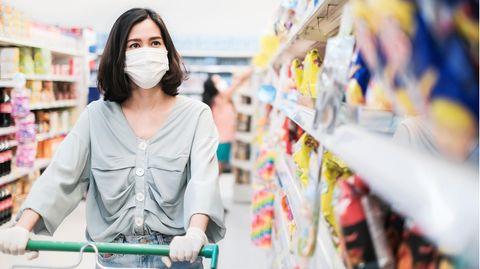Eine Frau schiebt ihren Einkaufswagen durch einen Supermarkt