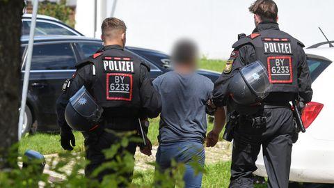 Zwei Einsatzkräfte der Polizei führen vor der Polizeiinspektion in Miesbach einen Tatverdächtigen ab