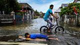 Auf einer überschwemmten Straße liegt ein schwarzhaariger Junge auf einem Surfbrett, während ein Jugendlicher Rad fährt