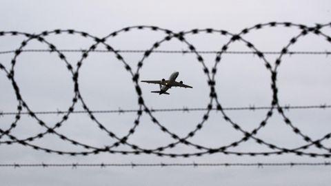 Ein Flugzeug startet am Flughafen Hannover – fotografiert durch Stacheldraht am Flughafenzaun