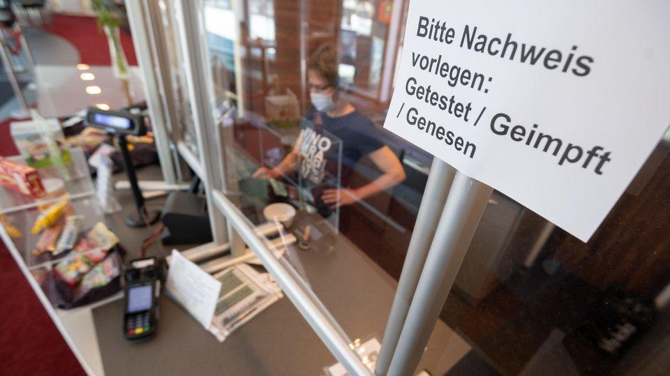 """Ein Schild """"Bitte Nachweis vorlegen: Getestet, Geimpft, Genesen"""" hängt an der Kasse von einem Kino"""