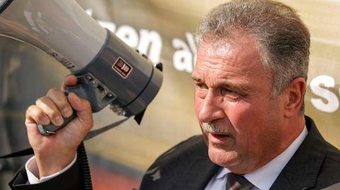 Ein weißer Mann in Anzug und Krawatte steht im Sonnenschein, während er in ein Megafon spricht. Er hat einen graue Haare